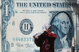 An Egyptian vender adjusts her veil in front of a giant poster of a US dollar outside an exchange office in Cairo, Egypt, March 28, 2011.