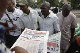 People read newspapers with election headlines on the street in Abuja, Nigeria Monday, March 30, 2015. Nigerians are waiting  for results of the tightest and most bitterly contested presidential election in the nation's turbulent history.  (AP Photo/