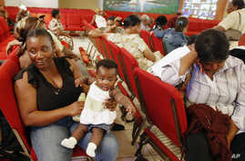 FILE - Haitian national Carole Manigat, left, holds her daughter Hadassa Carole Albert as she waits for her turn to fill out temporary protective status papers at Notre Dame d'Haiti Catholic Church in the Little Haiti neighborhood in Miami, Jan. 21,