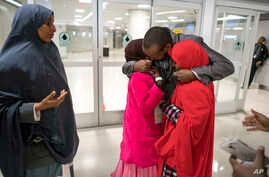 Ismail Issack, father of Miski Shalle, 11, and Muzamil Shalle, 14, embraces his children as their mother Halima Mohamed, far left, looks on as they reunite for the first time in seven years at John F. Kennedy International Airport in New York.