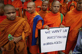 Buddhist monks hold a placard as they protest in front of the U.N. office in Bangkok, October 3, 2012.