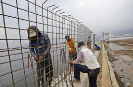FILE - Workers build a wall which will be used as a barrier to prevent sea water from flowing onto land and cause flooding in Jakarta, Indonesia, Dec. 8, 2015.