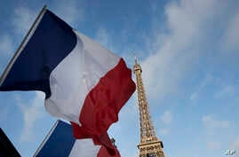 French flags fly as the closed Eiffel Tower is seen in the background on the first of three days of national mourning in Paris, Nov. 15, 2015.