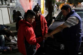 Migrant shelter director Jose Garcia, right, gives a few coins to two men from Guatemala on their way to cross into the United States in Tijuana, Mexico, Nov. 14, 2016.