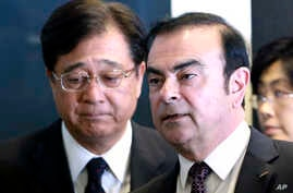 Nissan Motor Co. President and CEO Carlos Ghosn, right, and Mitsubishi Motors Corp. Chairman and CEO Osamu Masuko walk in the venue of their joint press conference in Yokohama, near Tokyo, Thursday, May 12, 2016.