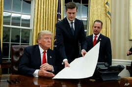 White House Chief of Staff Reince Priebus, right, watches as White House Staff Secretary Rob Porter, center, hands President Donald Trump a confirmation order for James Mattis as defense secretary, Jan. 20, 2017, in the Oval Office of the White House
