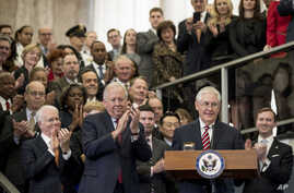 Secretary of State Rex Tillerson, center right, accompanied by State Department Undersecretary for Political Affairs Tom Shannon, center left, pauses while speaking to State Department employees upon arrival at the State Department in Washington, Feb