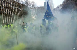 Demonstrators, called the yellow jackets, holds up an EU flag during a protest against rising fuel prices in Brussels, Friday, Nov. 30, 2018.