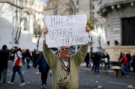 "A man holds a sign that reads in Spanish ""Macri stop it"" during a protest in Plaza de Mayo, Buenos Aires, Argentina, Aug. 22, 2017."
