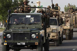 Pakistani army troops ride military vehicles following an operation launched against the Taliban in North Waziristan,  in Karachi, Pakistan, Monday, June 16, 2014. Pakistani jets pounded targets in the country's northwest on Monday as the military wa