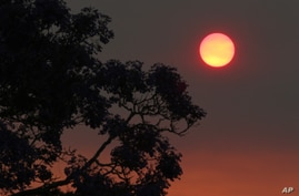 The sun glows a deep orange color as the light is filtered through smoke haze from wildfires drift over Sydney October 20, 2013.