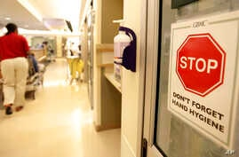 FILE- A sign urging staff and patients to wash their hands hangs on the wall as a patient is wheeled through the emergency room at Greater Baltimore Medical Center in Towson, Maryland, Nov. 3, 2009.