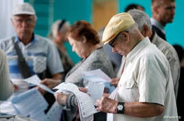 People visit a polling station during a parliamentary election in Stavropol, Russia, Sept. 18, 2016.