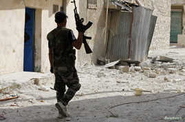 A Free Syrian Army fighter carrying a weapon, walks on rubble in Aleppo's al-Amereya district October 1, 2012.