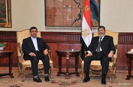 Egyptian President Mohamed Morsi (R), meets with Iran's President Mahmoud Ahmadinejad after he arrives at International Airport in Cairo in this photo provided by the Egyptian Presidency, February 5, 2013.