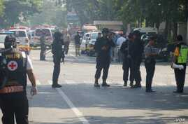 Police officers stand guard in front of a Catholic Church in Ngagel, Surabaya.