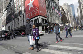 FILE - Macy's shoppers leave the retailer's flagship store in New York.