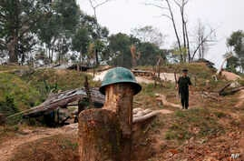 FILE - A Kachin Independence Army rebel walks at Hpalap mountain controlled by the Kachin rebels in northern Kachin state, Myanmar, March 17, 2018. The Kachin Independence Army along with other ethnic armed groups have been fighting against Myanmar a
