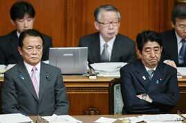Japanese Prime Minister Shinzo Abe (R) and Finance Minister Taro Aso (L) show their sour faces at the Upper House's plenary session at the National Diet in Tokyo, February 6, 2013.