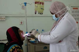 Nahla Arishi, a pediatrician, checks a woman infected with diphtheria at the al-Sadaqa teaching hospital in the southern port city of Aden, Yemen, Dec. 18, 2017.