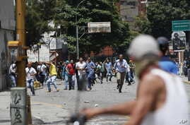 Pro-government supporters confront anti-government protesters in Caracas, Venezuela, July 20, 2017.