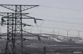 Power lines and wind turbines are seen at a wind and solar energy storage and transmission power station of State Grid Corporation of China, in Zhangjiakou of Hebei province, China, March 18, 2016.