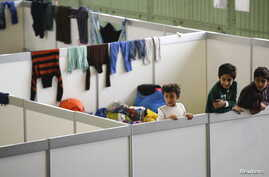 FILE - Children watch as they stand on beds in a shelter for migrants inside a hangar of the former Tempelhof airport in Berlin, Germany, Dec. 9, 2015.