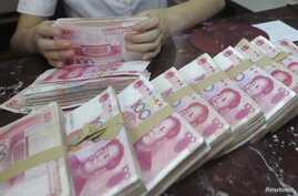 An employee counts Chinese 100 yuan banknotes at a branch of Bank of Communications in Shenyang, Liaoning province July 6, 2012.