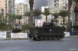 Smoke rises as a Lebanese Army armed vehicle drives through a street in Tripoli, northern Lebanon, Dec.1, 2013.