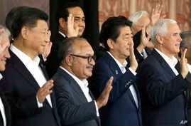From left, Chinese President Xi Jinping, Papua New Guinea's Prime Minister Peter O'Neill, Japanese Prime Minister Shinzo Abe, and U.S. Vice President Mike Pence wave as they pose for a group photo at APEC Haus in Port Moresby, Papua New Guinea, Nov.