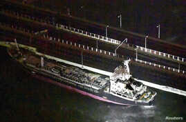A 2,591-tonne tanker, which is sent by strong wind caused by Typhoon Jebi, crashes into a bridge connecting Kansai airport, which is built on a man-made island in a bay, to the mainland, in Izumisano, western Japan, in this photo taken by Kyodo, Sept