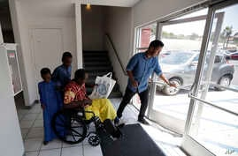 Ali Said, of Somalia, leaves a center for refugees with his two sons, as refugee caseworker Mohamed Yassin, right, holds open the door, July 6, 2017, in San Diego. Said, whose leg was blown off by a grenade, says he feels unbelievably lucky to be amo