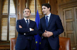 FILE _ French President Emmanuel Macron and Canadian Prime Minister Justin Trudeau wait for the start of a photo opportunity in Trudeau's office on Parliament Hill in Ottawa, Ontario, Canada, June 6, 2018.