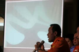 Chief of National Search And Rescue Agency (BASARNAS) F. Henry Bambang Soelistyo, lower right, shows an underwater photo of a part of the wreckage of AirAsia Flight 8501 found by divers in Java Sea, during a press conference in Jakarta, Indonesia, We...