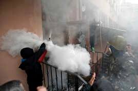 A pro-Russian protester fires a fire extinguisher at riot police inside at a police station building in Odessa, Ukraine, Sunday, May 4, 2014. Several prisoners that were detained during clashes that erupted Friday between pro-Russians and government