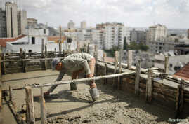 A Palestinian worker flattens cement on the roof of a building under construction in Gaza City, Sept. 22, 2013.