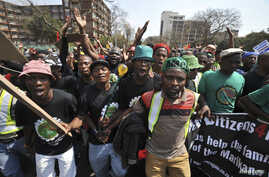 Miners from Marikana, along with their families and supporters, march to the Union Buildings in Pretoria, to protest the government's lack of legal funding for the Marikana commission of inquiry, Sept. 12, 2013.