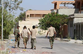 Fighters from the pro-government forces loyal to Libya's Government of National Unity (GNA) walk on August 3, 2016 in Sirte during an operation against jihadists of the Islamic State (IS) group.