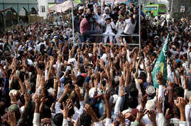 Supporters of the Tehreek-e-Labbaik Pakistan (TLP) Islamist political party raise their hands as they listen to the speech of their leader during a protest march to condemn a cartoon competition by the Netherlands, in Lahore, Pakistan, Aug. 29, 2018.