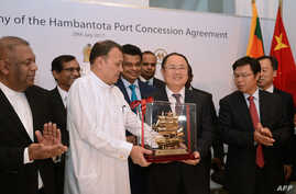 Sri Lanka's Minister of Ports & Shipping Mahinda Samarasinghe (C) exchanges souvenirs with Executive Vice President of China Merchants Port Holdings Dr. Hu Jianhua (3-R) during the Hambantota International Port Concession Agreement at a signing cerem