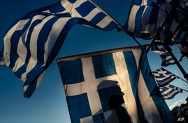 A pro-euro demonstrator is silhouetted behind a Greek flag during a rally outside the Greek Parliament in Athens, June 22, 2015.