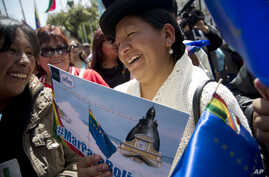 """An Aymara indigenous woman holds a poster that reads in Spanish """"Sea for Bolivia"""" during a rally in La Paz in support of Bolivia's bid for access to the Pacific Ocean, Sept. 24, 2015."""