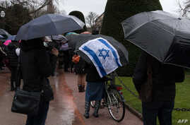 FILE - People take part in a slient march in Strasbourg, France, March 28, 2018, in memory of an 85-year-old Jewish woman murdered in her home in what police believe was an anti-Semitic attack.