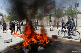 Afghan protesters set a fire during a protest in Kabul, Afghanistan, June 2, 2017. A rally against the government Friday following Wednesday's devastating truck bomb attack in Kabul saw hours of angry confrontation between protesters and police.