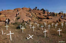 """Members of South Africa's mining community walk near crosses placed at a hill known as the """"Hill of Horror"""", where 43 miners died during clashes with police last year at Lonmin's Marikana platinum mine in Rustenburg, northwest of Johannesburg, May 14"""