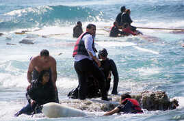 A man rescues an migrant from the Aegean sea, in the eastern island of Rhodes, April 20, 2015.