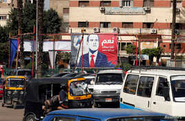 """People and vehicles are seen near a poster of Egypt's President Abdel Fattah al-Sisi for the upcoming presidential election, which reads """"Yes, All of us with you for Egypt"""", in Cairo, Feb. 28, 2018."""