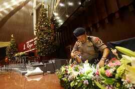 Members of a police bomb squad search for suspicious materials prior to the Christmas Eve Mass at the Messiah Cathedral in Jakarta, Indonesia, Dec. 24, 2014.