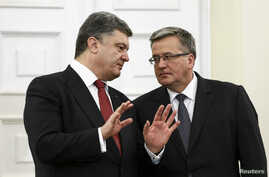 Ukrainian President Petro Poroshenko (L) speaks with Polish President Bronislaw Komorowski during their meeting in Warsaw, Dec. 17, 2014.