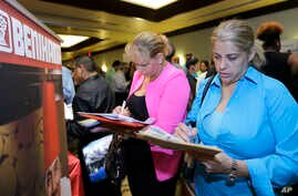 FILE - Job seekers fill out employment applications at a job fair in Miami Lakes, Florida, Oct. 22, 2014.